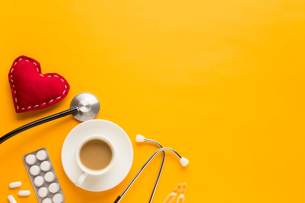 Coffee cup; blister packed tablets; stethoscope and stitched heart shape against yellow background