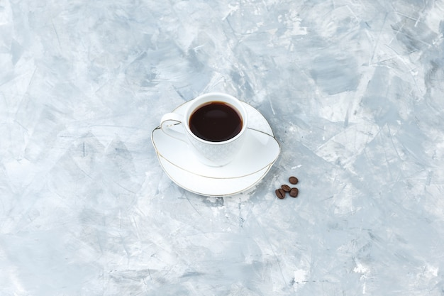 Coffee in a cup on a blue marble background. high angle view.