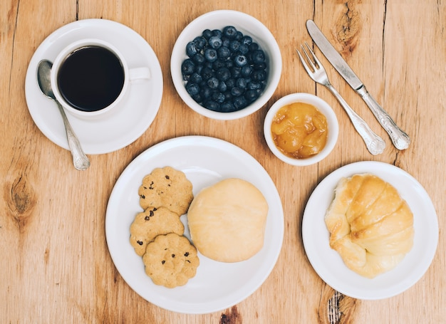Coffee cup; blueberries; jam; bread; bun and cookies on table