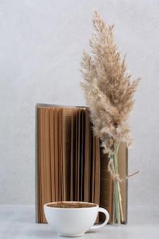 Кофейная чашка, книга и растение на сером столе