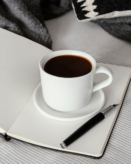 Coffee cup on book high angle
