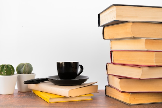 Coffee cup next to book pile