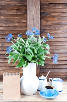 Coffee cup, bouquet of cornflowers and notebook on wooden background