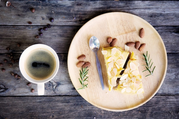 Coffee cup and cake on tray with a wooden background.