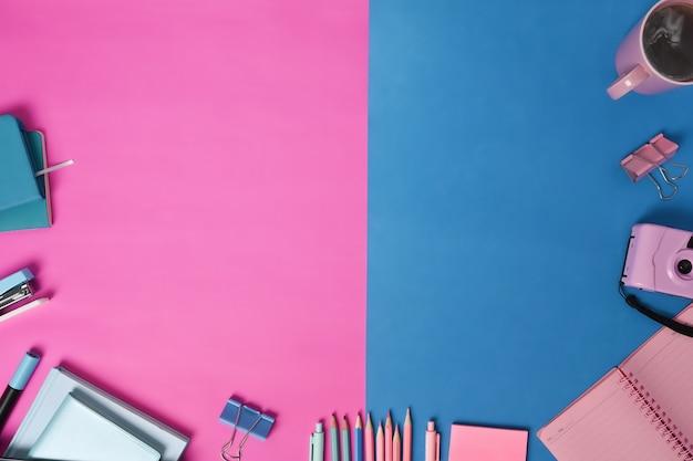 青とピンクのツートンカラーの背景にコーヒーカップ、カメラ、文房具。