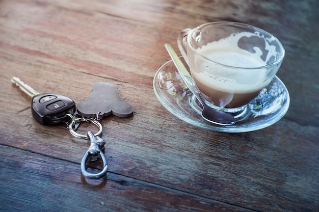Coffee cup and car keys on the wooden table.