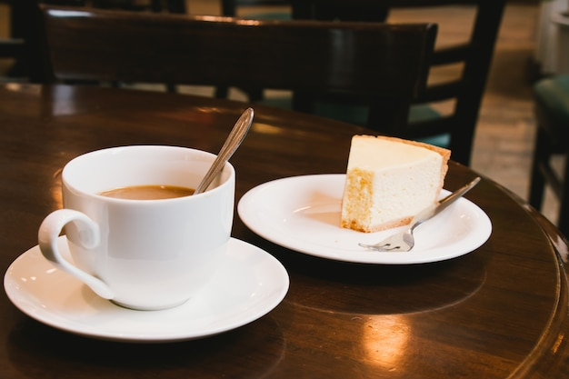 Coffee cup and cheesecake in coffee shop.