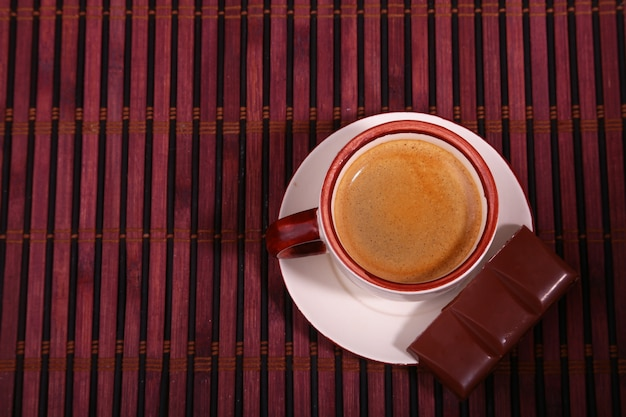 Coffee cup and chocolate on wooden table texture.
