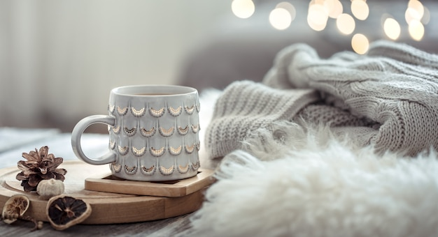 Coffee cup over christmas lights bokeh in home on wooden table with sweater on a wall and decorations. holiday decoration, magic christmas