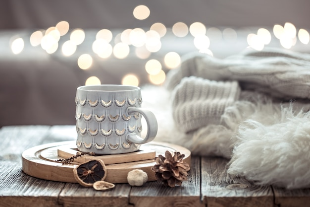 Coffee cup over christmas lights bokeh in home on wooden table with sweater on a wall and decorations. holiday decoration