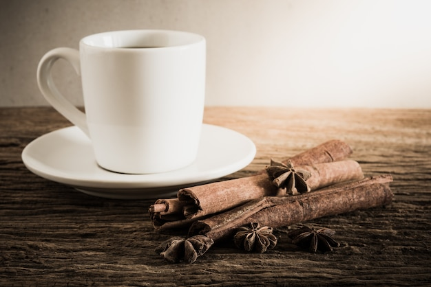 Coffee cup, cinnamon sticks on wooden table with against grunge wall. vintage tone , focus at spice