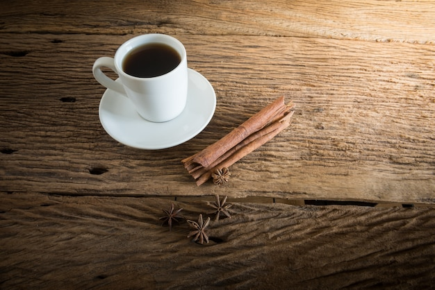 Coffee cup, cinnamon sticks on wooden table with against grunge wall. vintage tone
