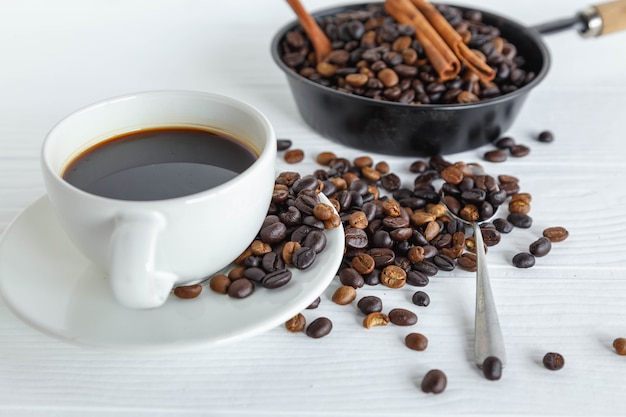 Coffee cup and coffee bean on white wooden table