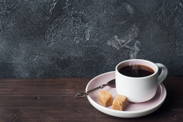 Coffee cup and coffee beans on dark background. copy space