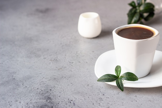 Coffee cup, coffee beans and milk jug on grey stone background copy space for text