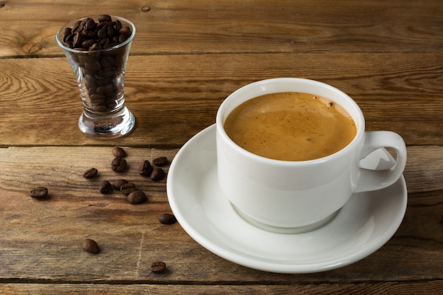 Coffee cup and coffee beans on rustic background