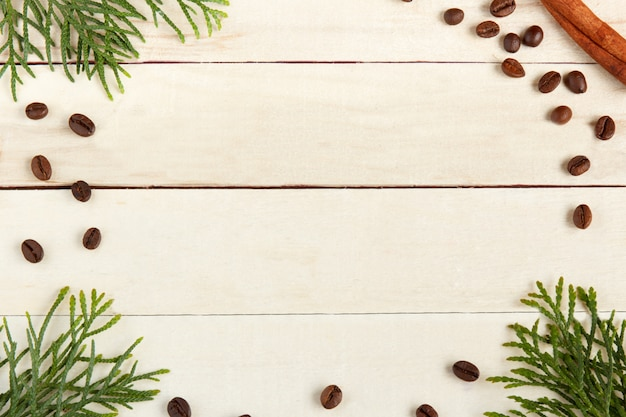 Coffee cup, coffee beans and spruce branches on wooden background.