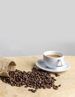 Coffee cup and coffee beans on table
