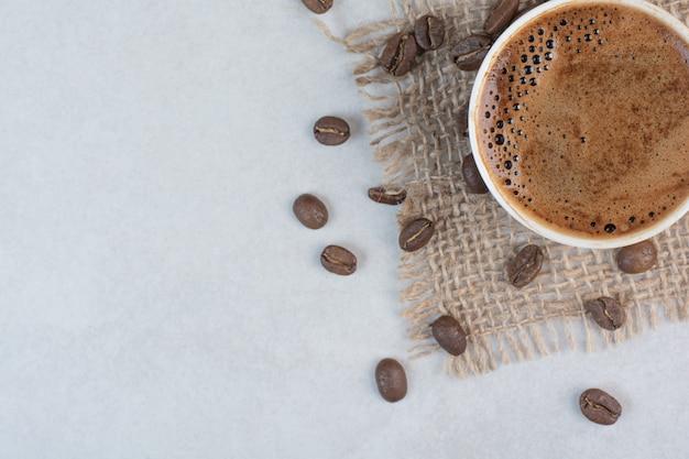 Tazza di caffè e chicchi di caffè su priorità bassa bianca. foto di alta qualità