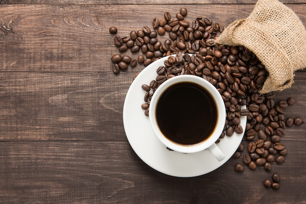 Coffee cup and coffee beans on wooden table. top view.