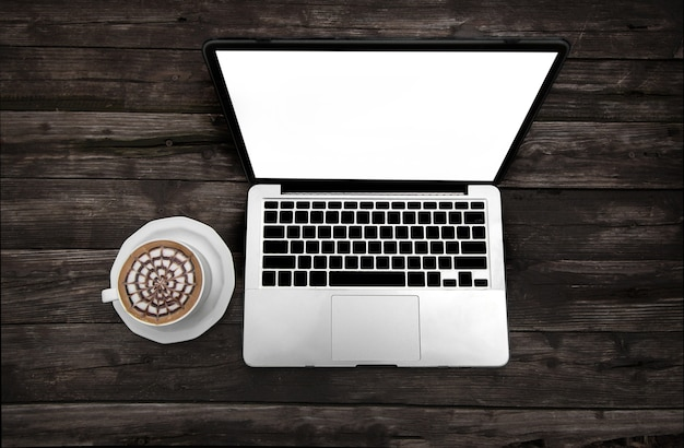 Coffee cup and computer on wood table