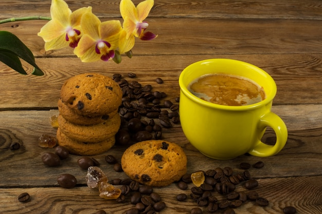 Coffee cup, cookies and yellow  orchid