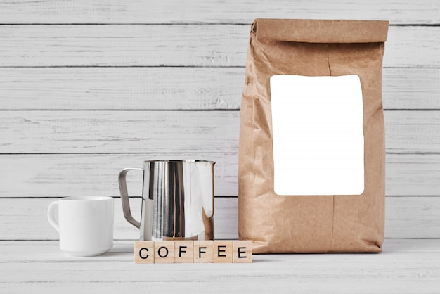 Coffee cup, craft paper bag and stainless pitcher