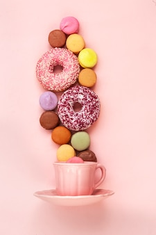 Coffee cup, delicious pink donuts with sprinkle and colorful bright macarons