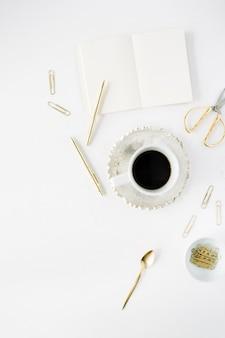 コーヒーカップ、空の日記、金色のアクセサリー:白地にティースプーン、ペン、クリップ、はさみ