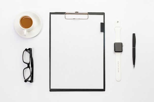 Coffee cup,eyeglasses,smart watch,pen and blank paper clipboard on white desk
