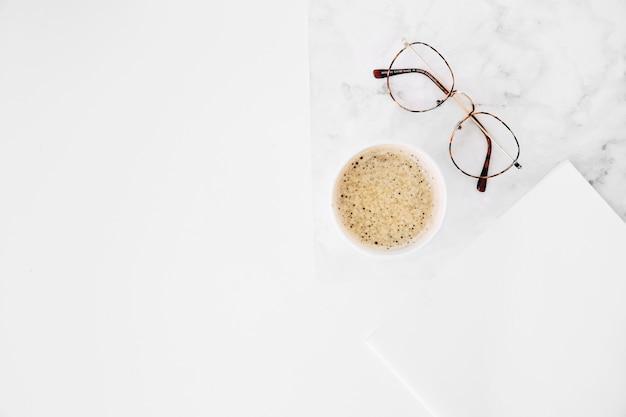 Tazza di caffè ed occhiali con carta bianca su fondo bianco