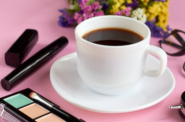 Coffee cup, flowers, mascara and glasses on pink surface.