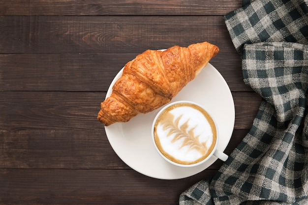 Coffee cup and fresh baked croissants near hand towel on wooden background. top view, copy space.