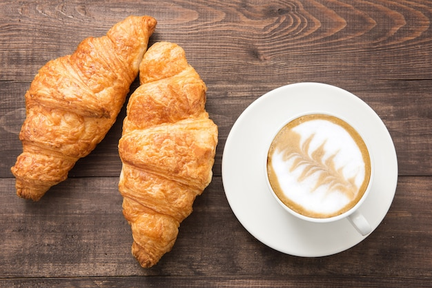 Coffee cup and fresh baked croissants on wooden background. top view
