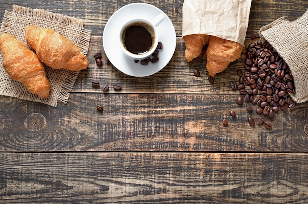 Coffee cup, freshly baked croissants, coffee beans on wood background - traditional breakfast concept with copy space. top view, flat lay.
