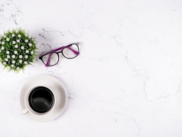 白い大理石の背景にコーヒーカップグラスと花瓶上面図コピースペース