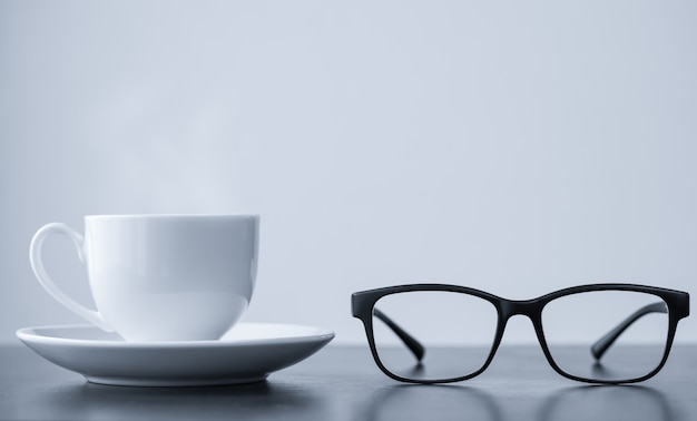 Coffee cup and glasses on desk