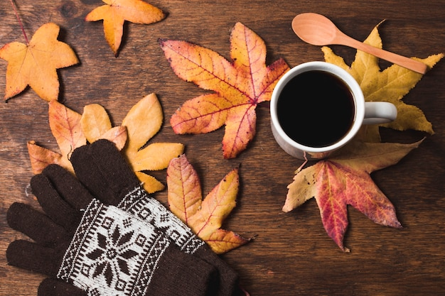 Coffee cup and gloves on autumn leaves background