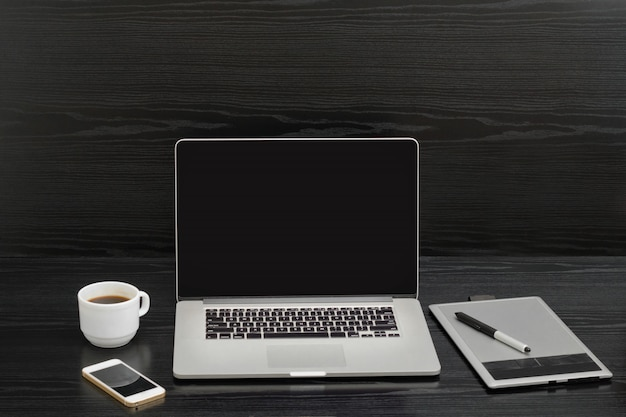 コーヒーカップ、スタイラス、ラップトップ、黒の木製テーブルの上の携帯電話とグラフィックタブレット