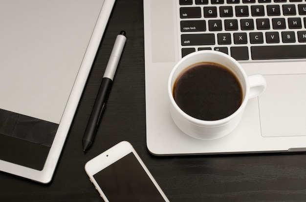 Coffee cup, graphics tablet with a stylus, part of laptop and phone on black wooden table, close-up