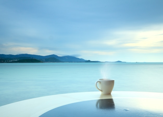 Coffee cup on grunge terrace on a seascape background