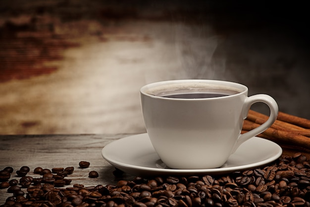 Coffee cup over grunge wooden background