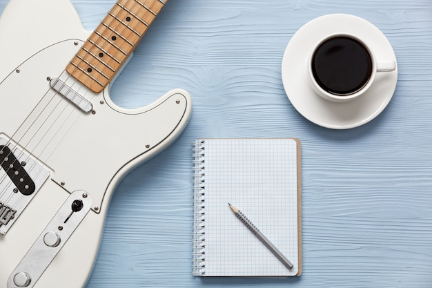 Coffee cup and guitar on wooden table with notebook and pencil