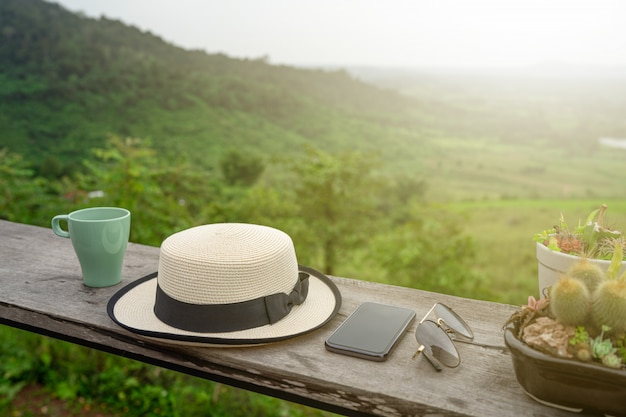 Coffee cup, hat, smartphone and glasses on wooden table