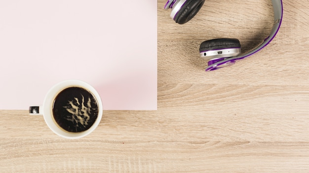 Coffee cup; headphone and blank paper on wooden background