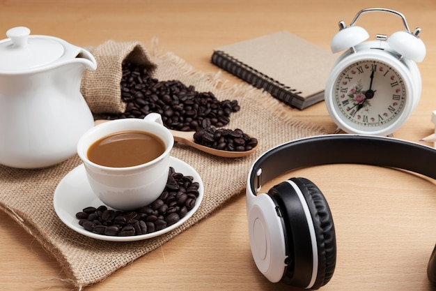 Coffee cup and headphone on wood plank background.