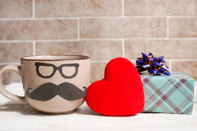 Кофейная чашка, сердце и подарочная коробка на деревянном столе. концепция праздника дня отца