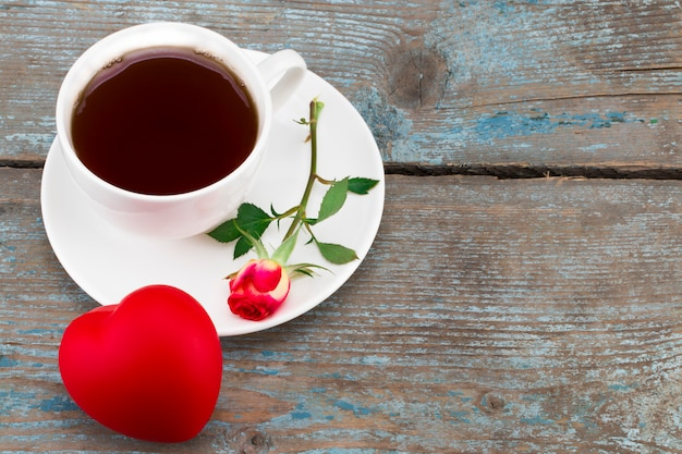 Coffee cup, heart and red rose wooden for valentines day with copy space Premium Photo