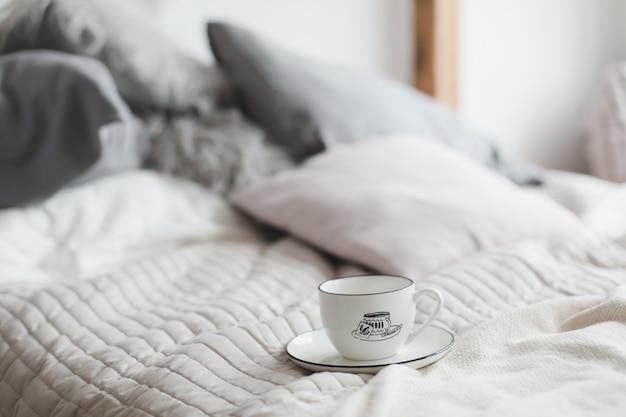 居心地の良いベッドのコーヒーカップ