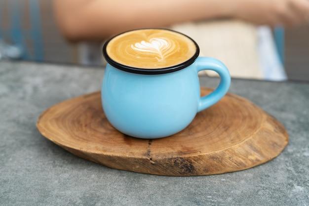 Кофейная чашка в синем стекле на деревянной тарелке